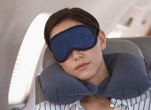 A businesswoman asleep on a flight